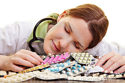 Doctor sleeping on heap of pills
