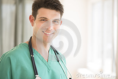 Doctor With Stethoscope Around Neck Smiling In Hospital