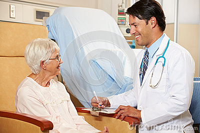 Doctor Taking Notes From Senior Female Patient Seated In Chair