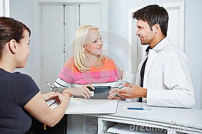 Doctor talking with senior woman at reception