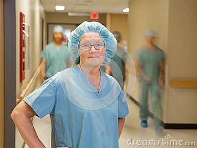 Doctor With Team Walking In Hospital Corridor