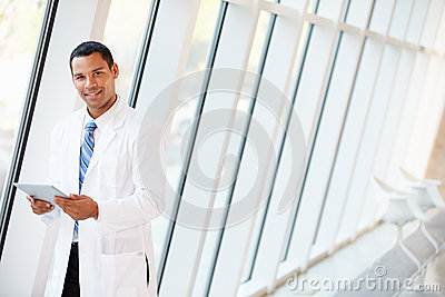 Doctor Using Digital Tablet In Corridor Of Modern Hospital