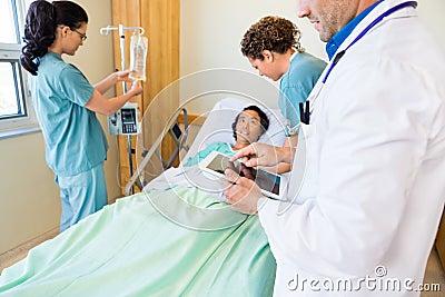 Doctor Using Digital Tablet With Nurses Examining