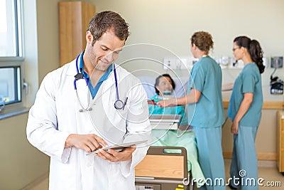 Doctor Using Digital Tablet While Nurses Serving