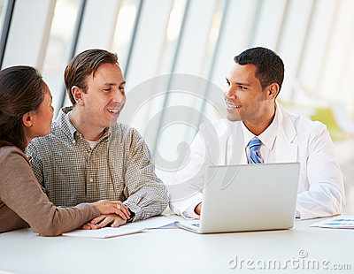 Doctor Using Laptop Discussing Treatment With Patients