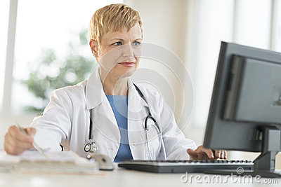 Doctor Working On Computer At Desk