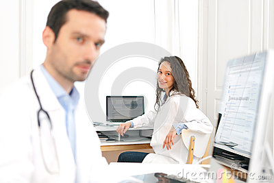 Doctor working at the office with nurse in background