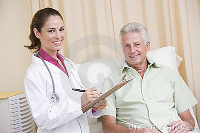 Doctor writing on clipboard giving checkup to man
