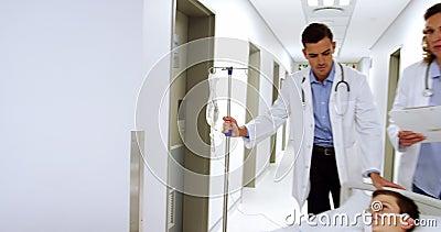Doctores que empujan la cama del ensanchador de la emergencia en pasillo almacen de video