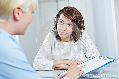 Doctors assistant giving form to patient