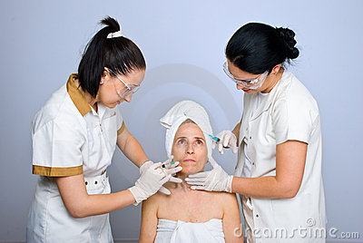 Doctors  injecting botox to senior woman