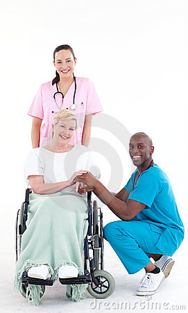 Doctors with a patient in a wheel chair smiling