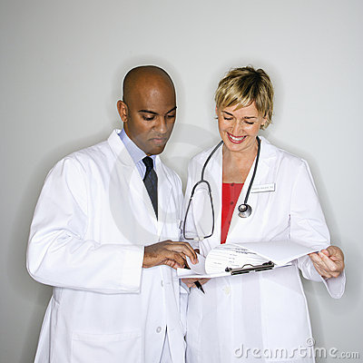 Doctors reading paperwork.