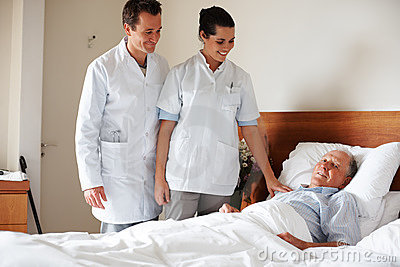 Doctors visiting a senior patient at his bed