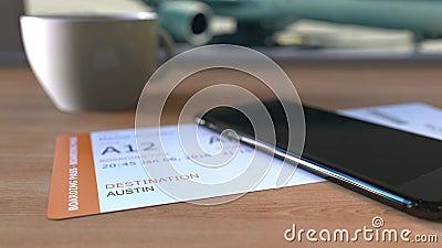 Documento de embarque a Austin y smartphone en la tabla en aeropuerto mientras que viaja a los Estados Unidos almacen de metraje de vídeo