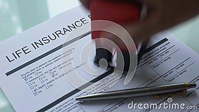 Documento rejeitado do seguro da vida, mão que carimba o selo no papel oficial filme