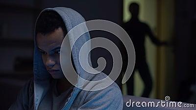 Doen schrikken Afrikaanse Amerikaanse tienerzitting in duisternis mannelijke openingsdeur, geweld stock footage
