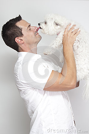 Dog licking nose of man