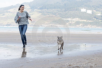Dog and woman running and playing in the beach.