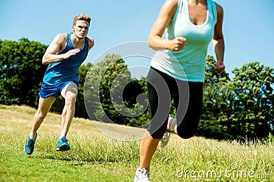 Dois atletas que correm através dos prados