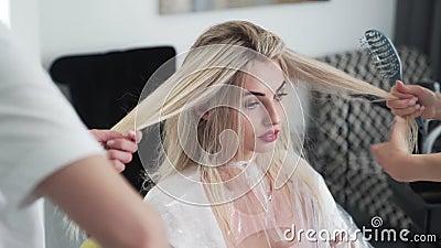 Dois cabeleireiros comb mulher longa loira após tingimento na barbearia filme