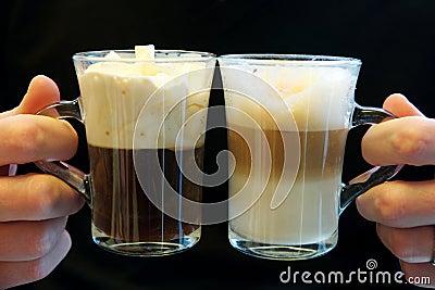 Dois cafés extravagantes nos copos de vidro, prendidos por duas mãos