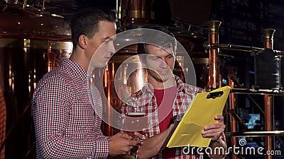 Dois cervejeiros que examinam a cerveja do ofício, trabalhando na cervejaria video estoque