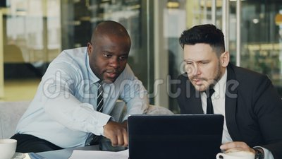 Dois colegas do negócio que olham o laptop e que discutem seus projetos no escritório moderno com as paredes de vidro video estoque