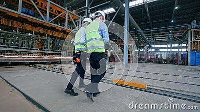 Dois engenheiros masculinos caminham pelo chão da fábrica industrial