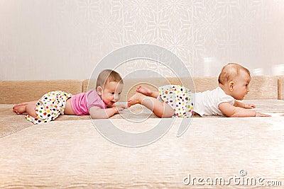 Dois gêmeos do bebê que rastejam um após o outro