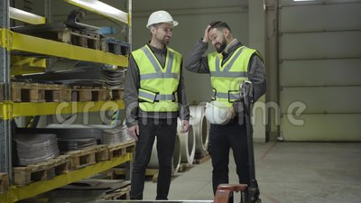 Dois homens cacasianos sorrindo em um depósito de metal de aço e conversando Trabalhadores que exercem a sua atividade no local d filme