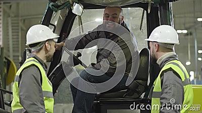 Dois homens caucasianos em capacetes e coletes conversando com um colega barbudo sentado em dois tratores Trabalhadores das fábri video estoque