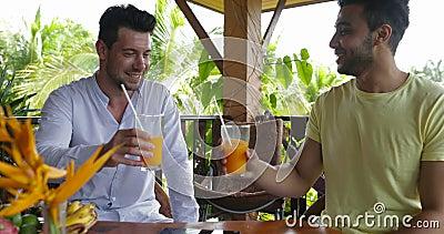 Dois homens que sentam-se no suco de laranja de fala da bebida do terraço do verão, par alegre da raça da mistura na manhã na cas video estoque