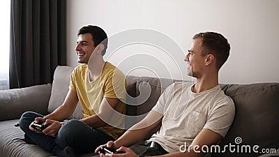 Dois indivíduos novos que jogam jogos de vídeo em casa, guardando manches e sentando-se no sofá cinzento na sala interior do sótã video estoque