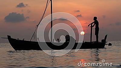 Dois pescadores lavam o barco velho no por do sol no Oceano Índico Movimento lento video estoque