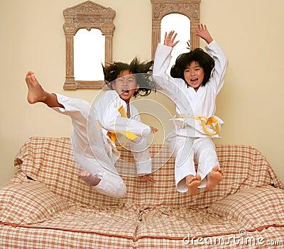 Dois poucos gils asiáticos do judo saltam no sofá