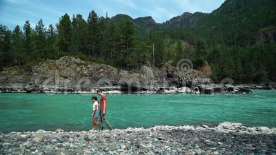 Dois povos felizes que andam ao longo da costa do rio da montanha Possibilidade remota vídeos de arquivo