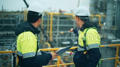 Dois trabalhadores do petróleo e gás que duscussing na indústria da refinaria filme