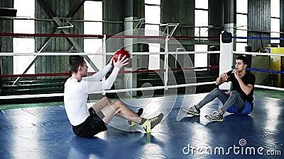 Dois trens musculares dos homens no gym que faz junto impulso-UPS para o abdômen e que joga a bola desportivo pesada durante vídeos de arquivo