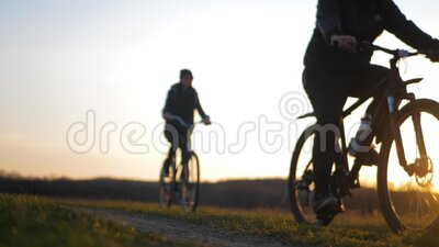 Dois turistas caminham de bicicleta na estrada Dois silhuetas de ciclistas em fundo solar Esporte e vida ativa vídeos de arquivo