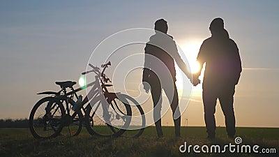 Dois turistas caminham de bicicleta na estrada Dois silhuetas de ciclistas em fundo solar Esporte e vida ativa filme