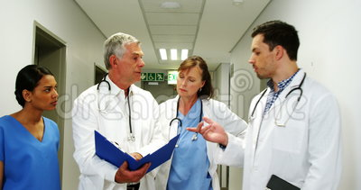 Doktoren und Krankenschwester, die über ärztlichem Attest beim Gehen im Korridor sich besprechen stock video footage