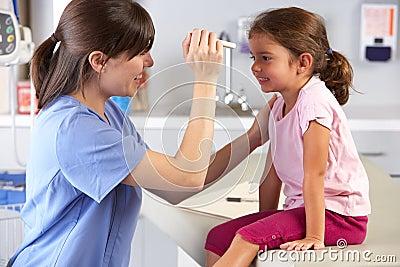 Doktorscy Egzamininuje dziecka oczy W lekarki biurze
