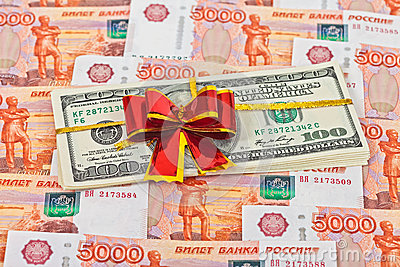 Dollar bills laying over rouble background