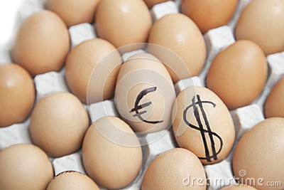 Dollar and euro sign on eggs surrounded by plain brown eggs in carton