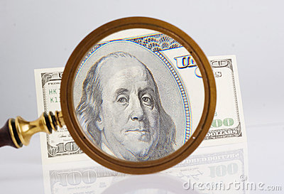 Dollar and magnifying lens