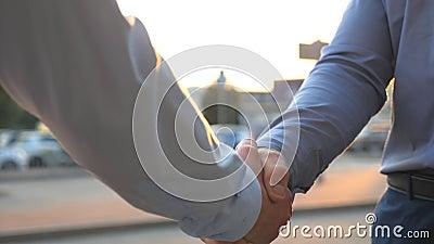 Dolly schot van twee jonge collega's die en handen ontmoeten schudden bij stadsstraat op zonsondergang Het succesvolle zakenliede stock video