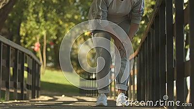 Dolore improvviso del ginocchio di sensibilità della donna di sport mentre pareggiando parco, sintomo di osteoartrite stock footage