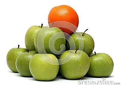 Domination concepts - orange on pyramyd of apples