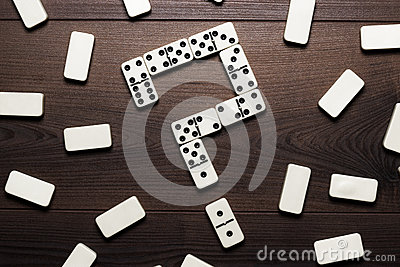 Domino pieces forming question mark on wooden